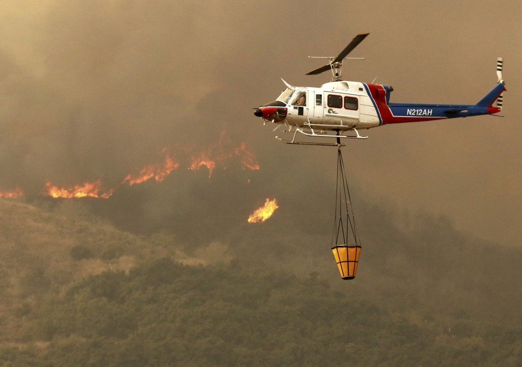 A helicopter makes a water drop on hot spots after the Thomas fire swept through Ventura, Calif., Tuesday, Dec. 5, 2017. (Daniel Dreifuss via AP)