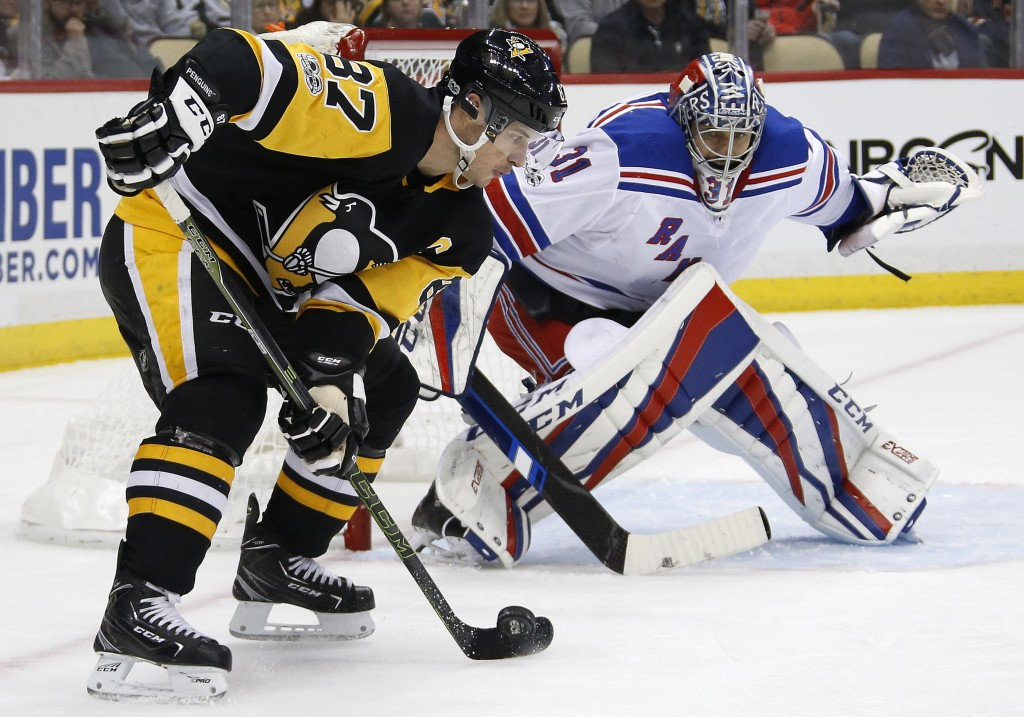 Pittsburgh Penguins' Sidney Crosby (87) works to get off a shot in front of New York Rangers goalie Ondrej Pavelec (31) during the second period of an