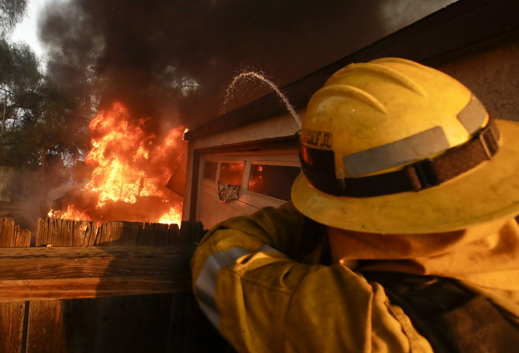 A Los Angeles County firefighter puts water a burning house in a wildfire in the Lake View Terrace area of Los Angeles Tuesday, Dec. 5, 2017. Ferociou