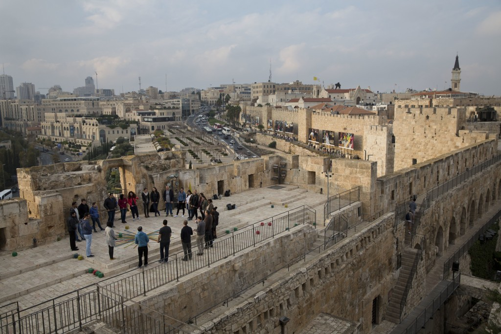 A group of Israelis play on the walls of Tower of David compound in Jerusalem, Tuesday, Dec. 5, 2017. U.S. officials say President Donald Trump will r