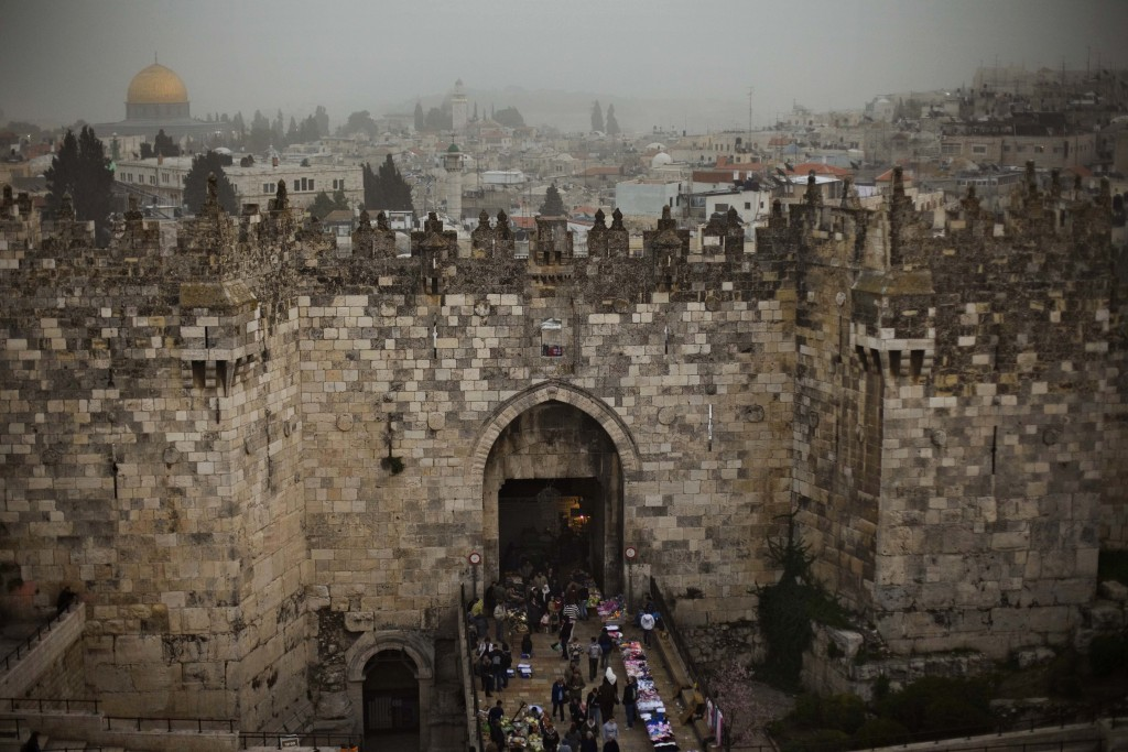 FILE- In this Feb. 19, 2009 ,file photo, people walk in and out of the Damascus gate, while the Dome of the Rock, background and left, is seen on a cl