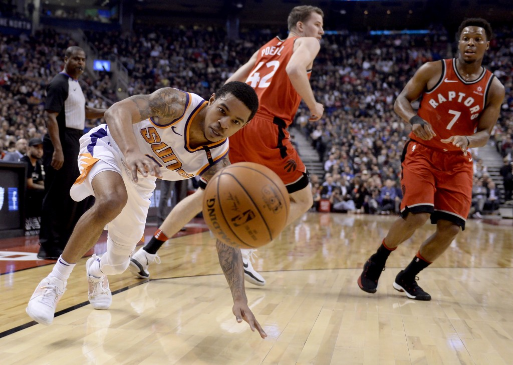 Phoenix Suns guard Tyler Ulis (8) dives for the ball as Toronto Raptors guard Kyle Lowry (7) and Jakob Poeltl (42) watch during the first half of an N