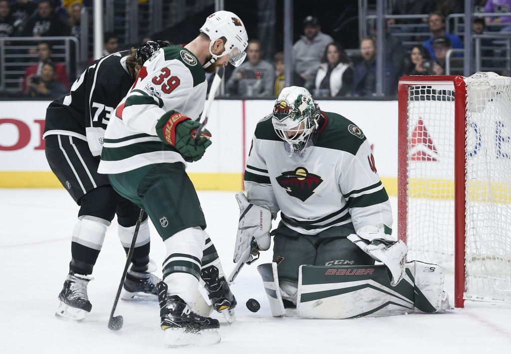 Minnesota Wild goalie Devan Dubnyk, right, makes a save as defenseman Nate Prosser, front, and Los Angeles Kings center Tyler Toffoli look for a rebou