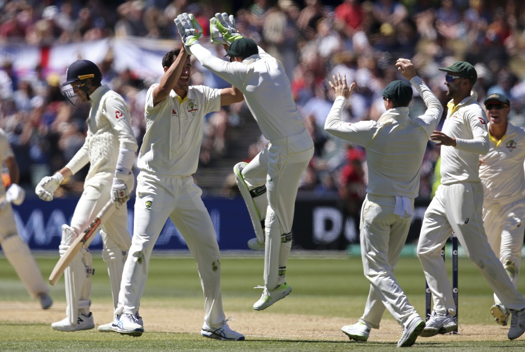 Australia's Mitchell Starc, second left, celebrates with teammates after taking the wicket of England's Craig Overton, left, during the fifth day of t