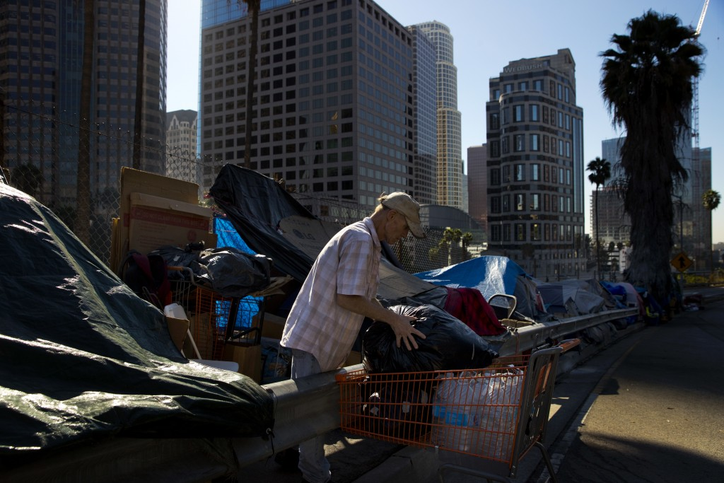 A man who identified himself just as Vincent, sorts his belongings outside his tent Friday, Dec. 1, 2017, in Los Angeles. Vincent said he thought he w