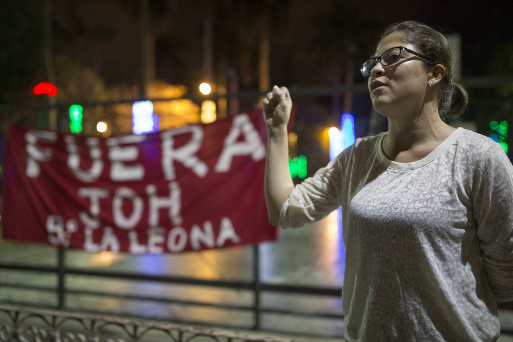 An anti-government demonstrator sings the Honduras national anthem protesting against the government imposed dawn-to-dusk curfew in Tegucigalpa, Hondu