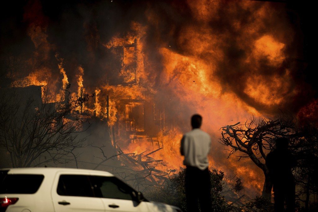 A man watches flames consume a residence as a wildfire rages in Ventura, Calif., Tuesday, Dec. 5, 2017. Ferocious winds in Southern California have wh