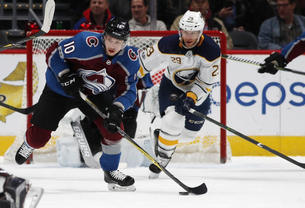 Colorado Avalanche right wing Sven Andrighetto, front, of Switzerland, picks up a loose puck in front of Buffalo Sabres right wing Jason Pominville in