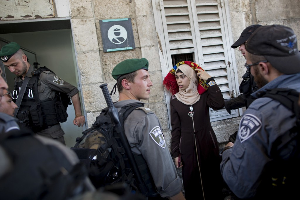 FILE - In this Wednesday, July 19, 2017 file photo Israeli border police officers stop a Palestinian woman for a security check as Palestinians gather