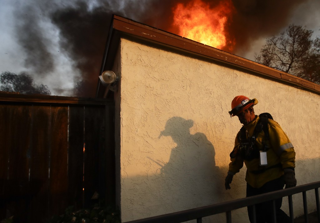 A Los Angeles County firefighter walks past burning house during a wildfire in the Lake View Terrace area of Los Angeles Tuesday, Dec. 5, 2017. Feroci