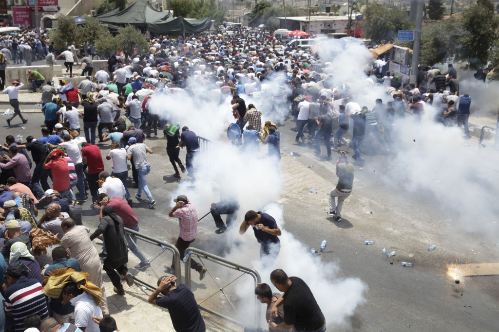 FILE - In this Friday, July 21, 2017, file photo, Palestinians run away from tear gas thrown by Israeli police officers outside Jerusalem's Old City.