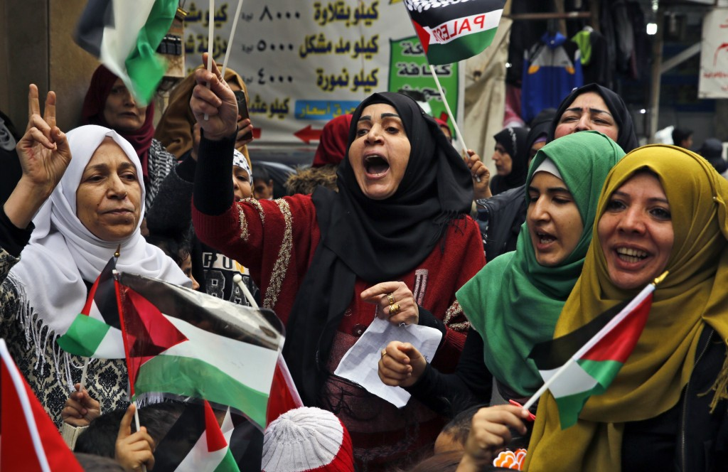 Palestinian women chant slogans as they hold Palestinian flags during a sit-in in the Bourj al-Barajneh Palestinian refugee camp, in Beirut, Lebanon,