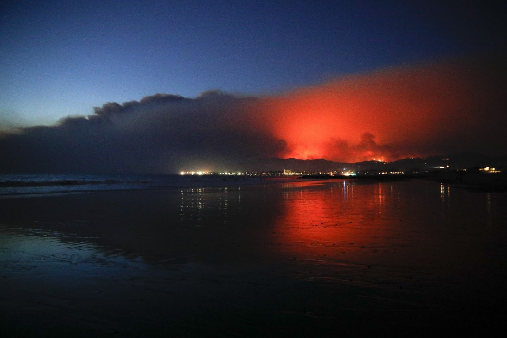 A wildfire continues to burn as its red glow is reflected on the beach Tuesday, Dec. 5, 2017, in Ventura, Calif. Raked by ferocious Santa Ana winds, e