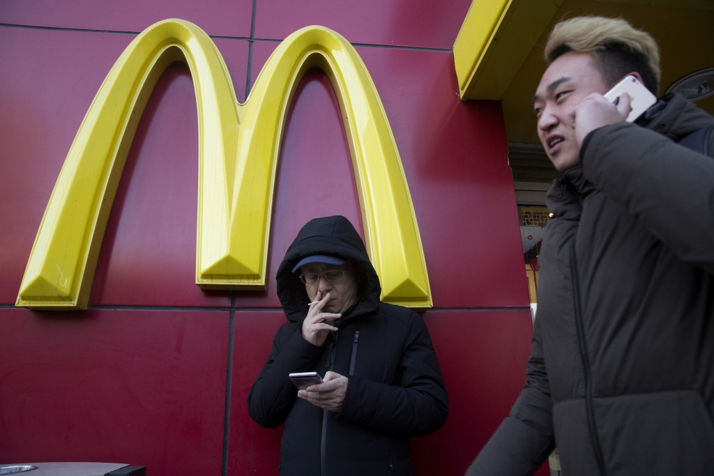 FILE - In this Jan. 10, 2017, file photo, a man smokes outside a McDonald's restaurant in Beijing. U.S. companies in China are seeing their sales impr
