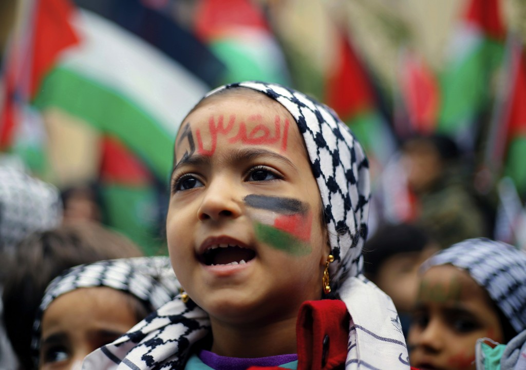 """A girl with a Palestinian flag and Arabic that read """"Jerusalem is for us"""" painted on her face chants slogans during a sit-in in the Bourj al-Barajneh"""