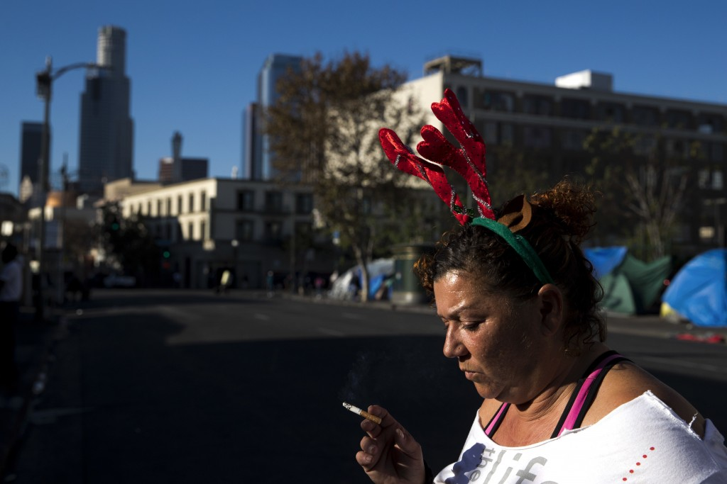 Wearing a Christmas headband, Grace Fernandez, who is homeless, smokes outside her tent in the Skid Row area of downtown Los Angeles, Friday, Dec. 1,