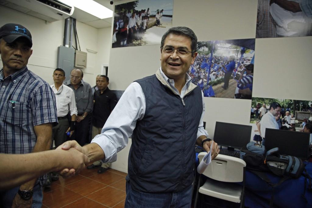 Honduran President Juan Orlando Hernandez shake hands with a journalist as he arrives for a press conference in Tegucigalpa, Honduras, Tuesday, Dec. 5