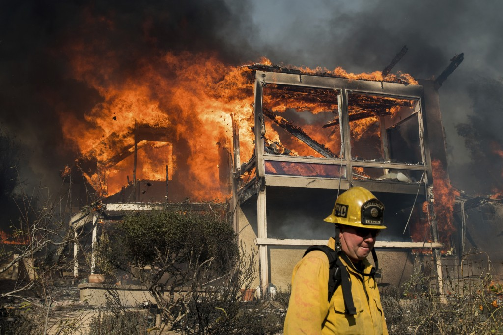 Mike Eliason, a public information officer with Santa Barbara County Fire, passes a burning home as a wildfire rages in Ventura, Calif., on Tuesday, D