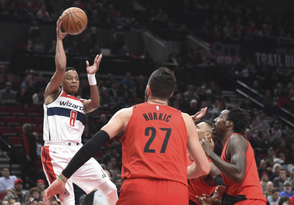 Washington Wizards guard Tim Frazier passes the ball over Portland Trail Blazers center Jusuf Nurkic during the first half of an NBA basketball game i