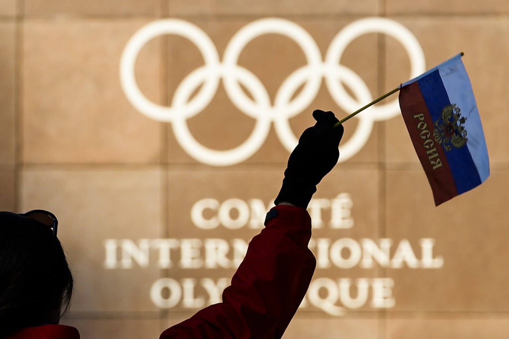 A woman waves a Russian flag outside of the International Olympic Committee (IOC) headquarters in front of the Olympic Rings prior to the opening of t