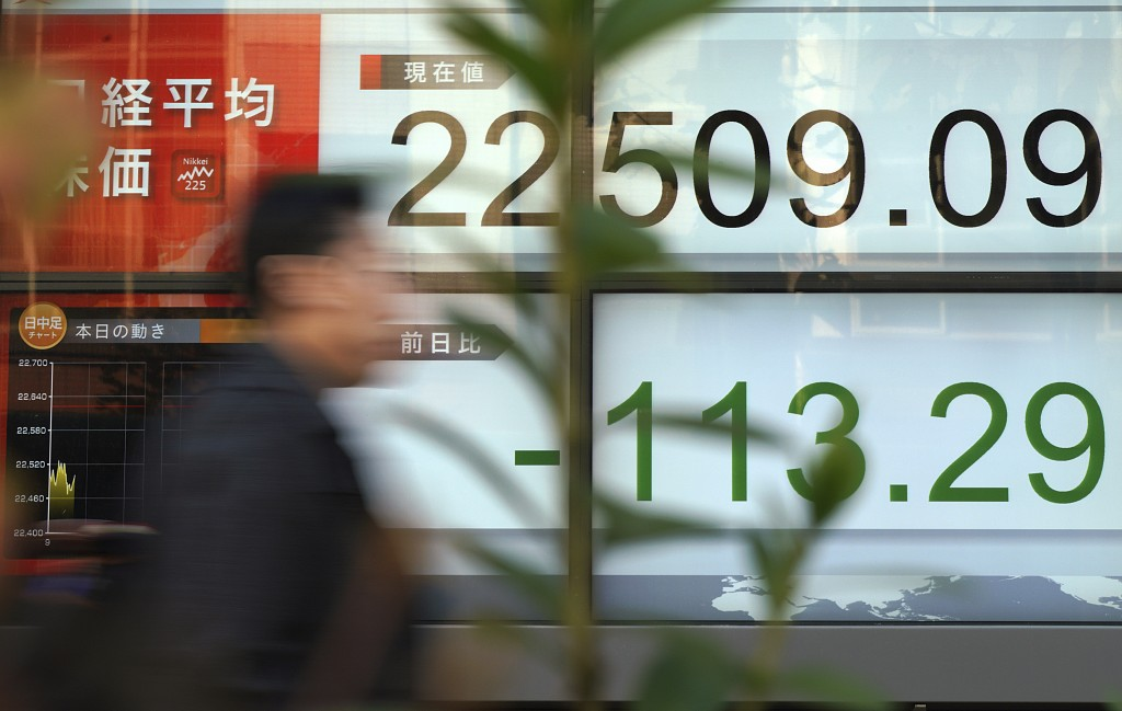 A man walks past an electronic stock board showing Japan's Nikkei 225 index at a securities firm in Tokyo Wednesday, Dec. 6, 2017. Shares in Asia fell