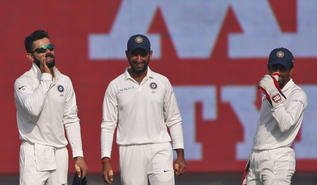 India's wicket-keeper Wriddhiman Saha, right, and Cheteshwar Pujara, center, smile as they hear captain Virat Kohli, left, call out to teammate Mohamm