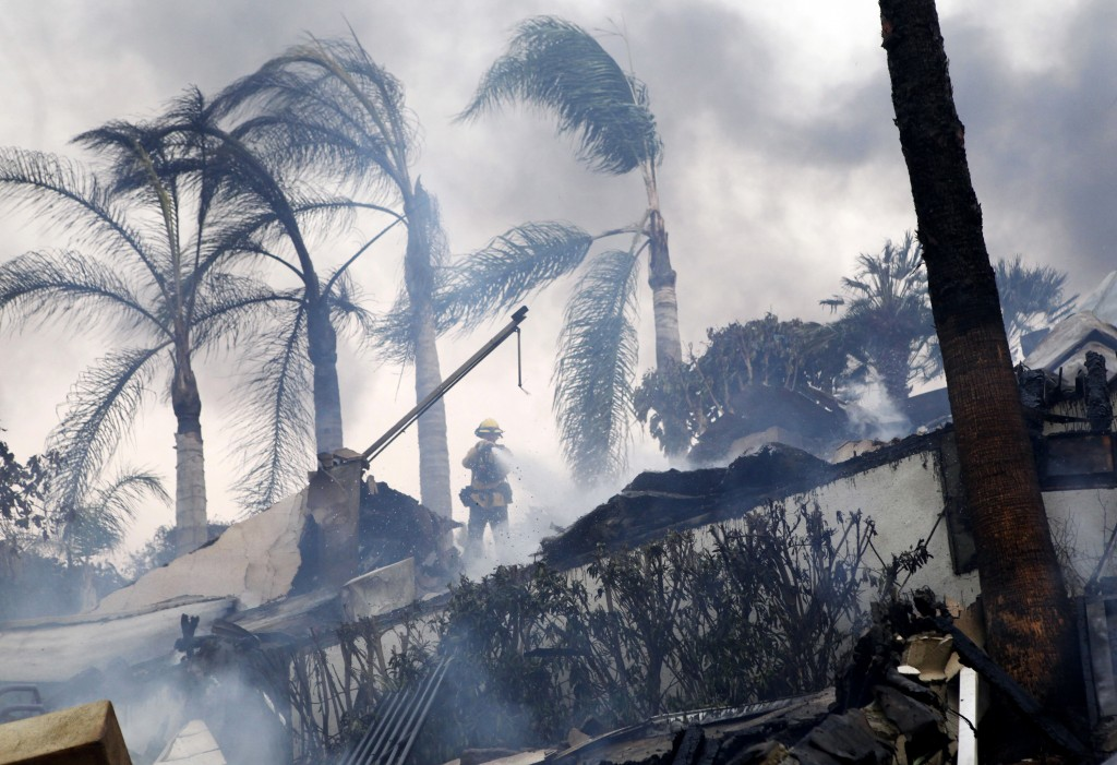 A firefighter stands under windswept palm trees as he hoses down smoldering debris in Ventura, Calif., Tuesday, Dec. 5, 2017. Ferocious Santa Ana wind