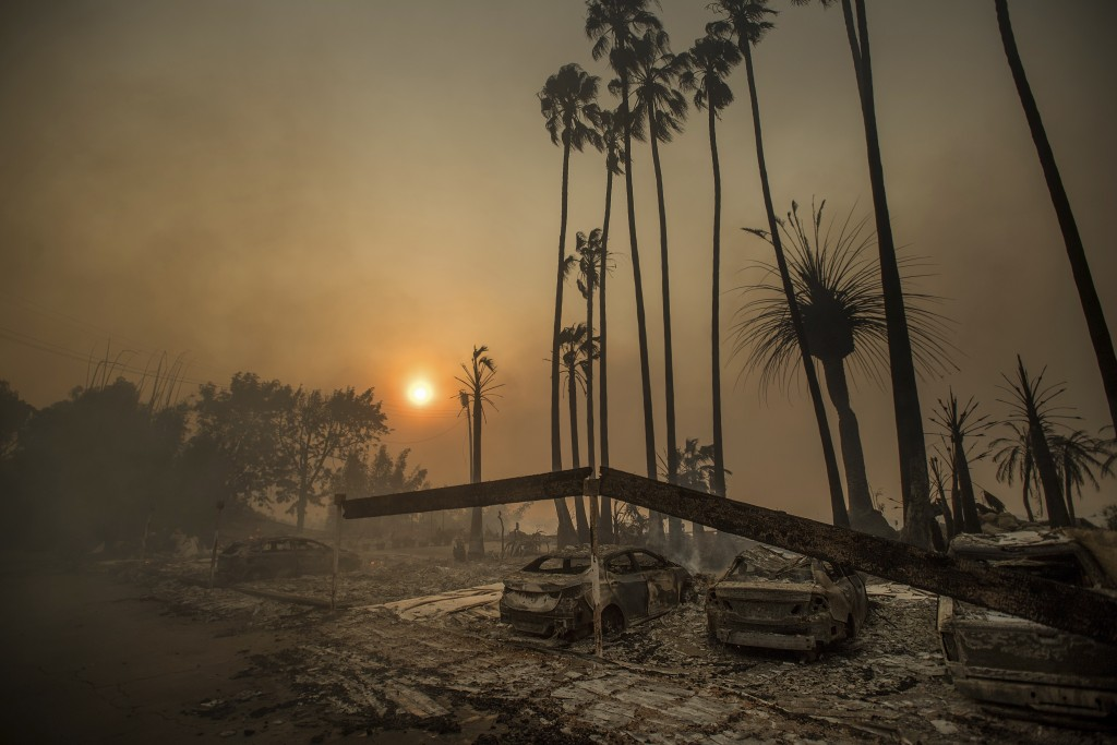 Smoke rises behind a leveled apartment complex as a wildfire burns in Ventura, Calif., on Tuesday, Dec. 5, 2017. Over 100 structures have burned so fa