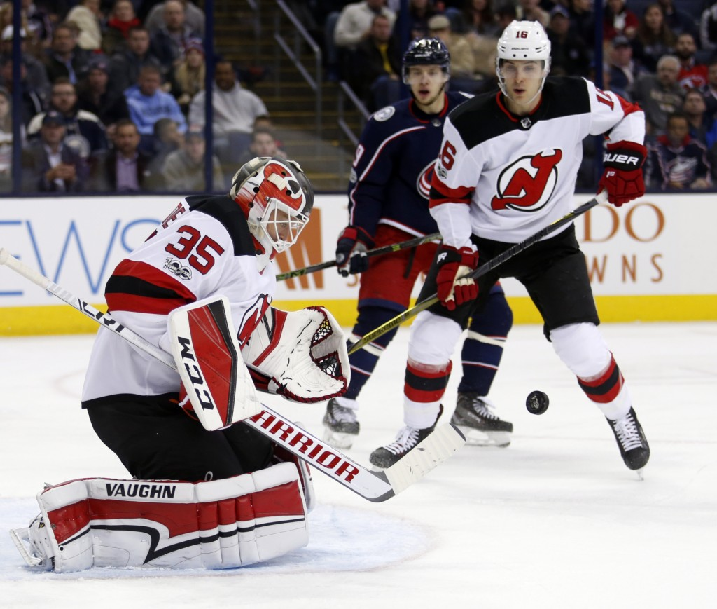 New Jersey Devils goalie Cory Schneider, left, stops a shot in front of Columbus Blue Jackets forward Artemi Panarin, center, of Russia, and Devils Ne