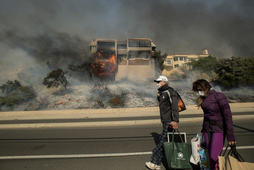 James and Josie Ralstin carry belongings from their Ventura, Calif., home as flames from a wildfire consume another residence on Tuesday, Dec. 5, 2017