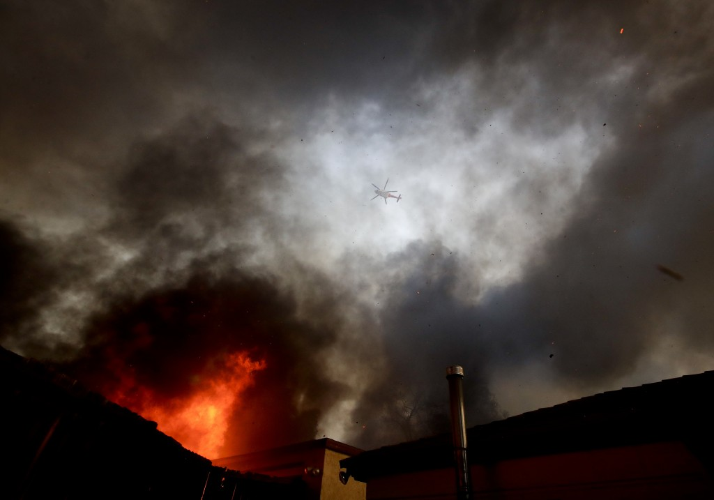 A water dropping helicopter flies over a hot spot on the Creek Fire in the Lake View Terrace area of Los Angeles, Tuesday, Dec. 5, 2017. (AP Photo/Chr