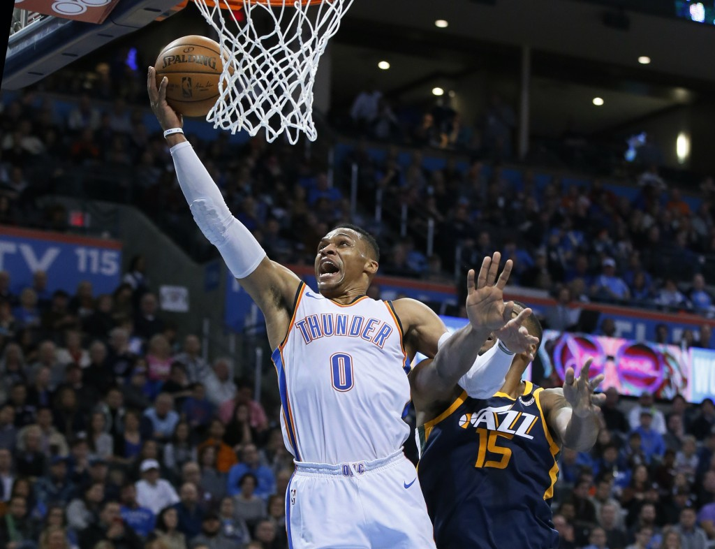 Oklahoma City Thunder guard Russell Westbrook (0) shoots in front of Utah Jazz forward Derrick Favors (15) in the second quarter of an NBA basketball