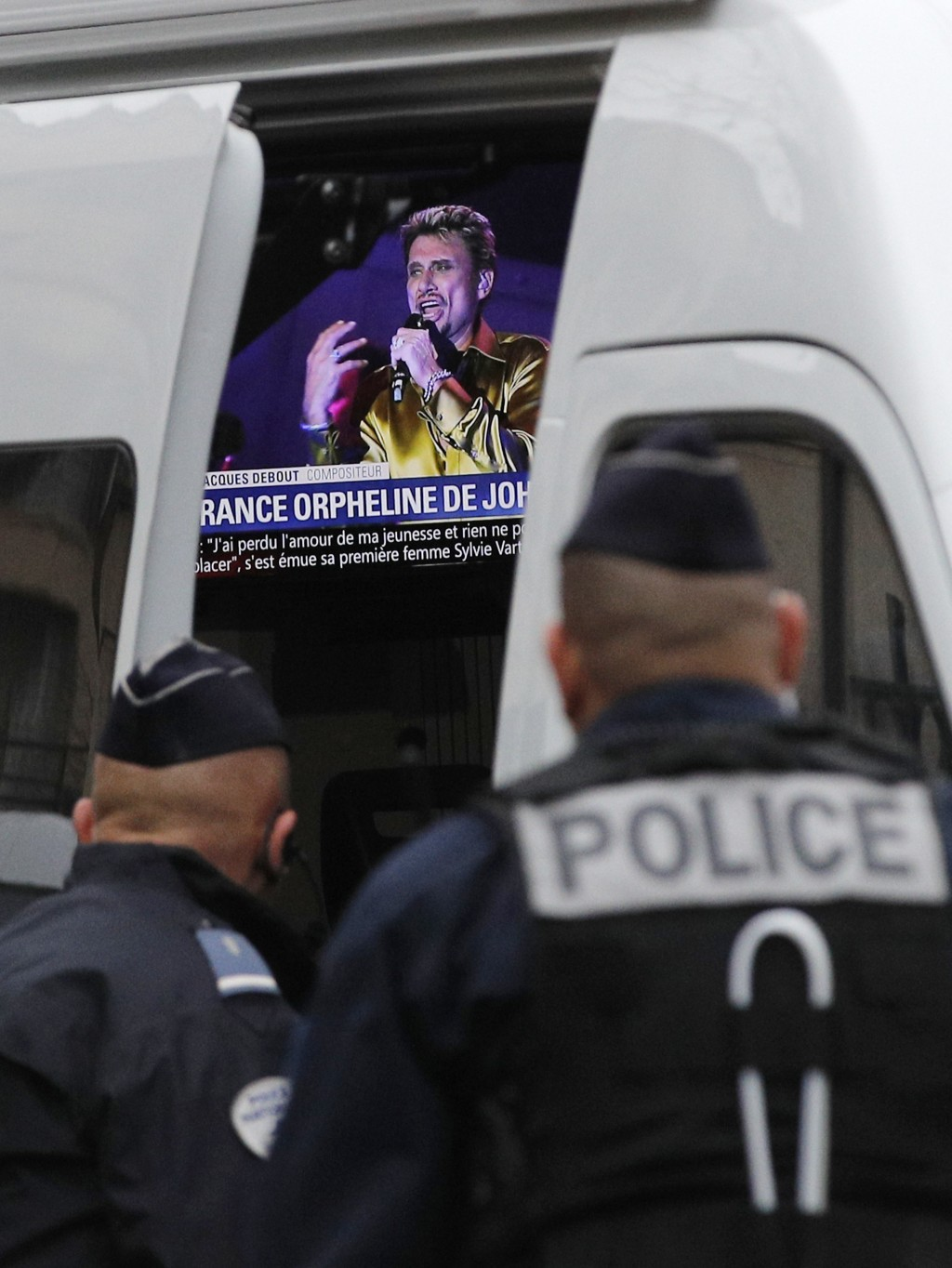 French police officers watch a television set up in a police car and airing a tribute to Johnny Hallyday, outside Johnny Hallyday's house in Marnes-la