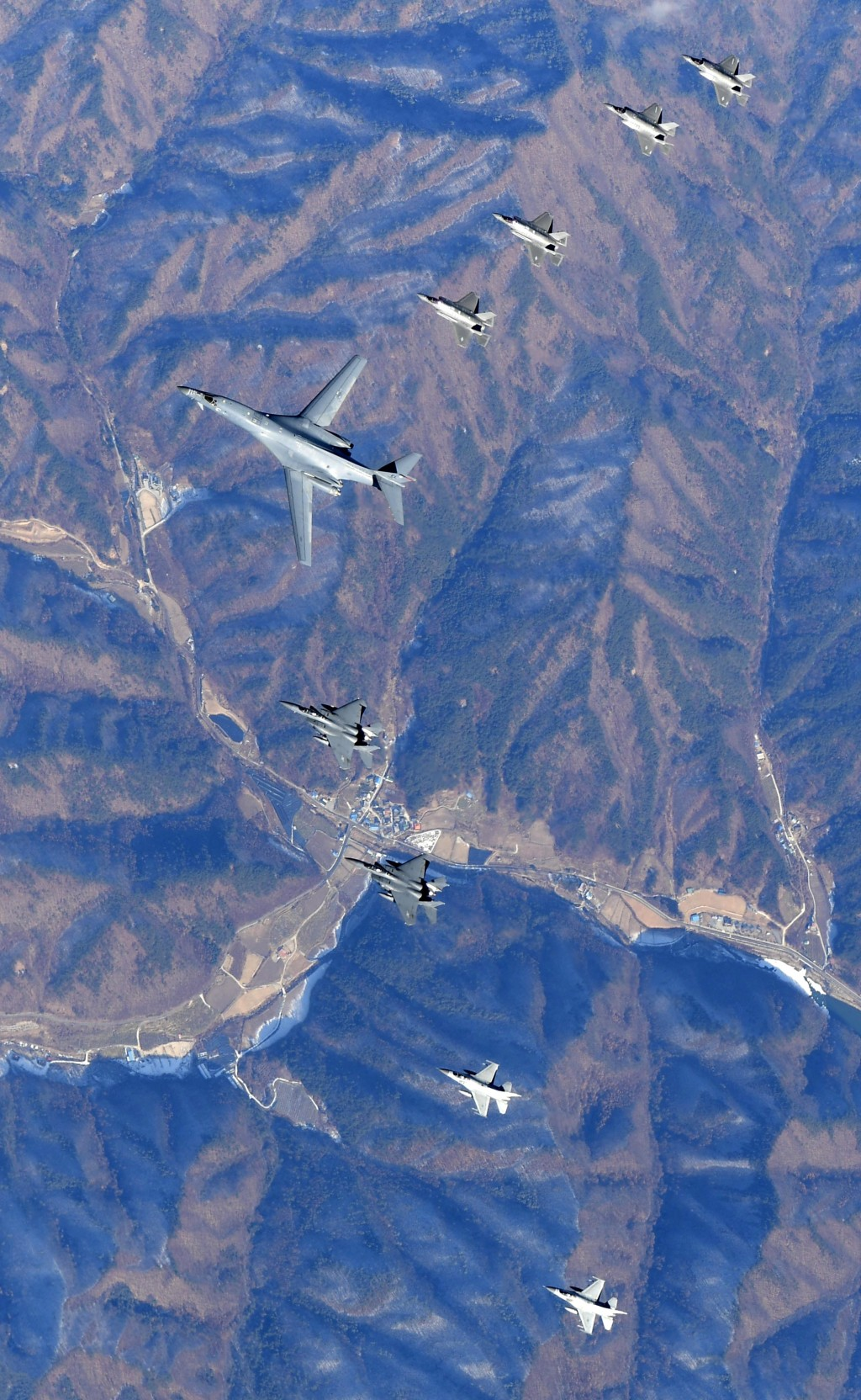 In this photo provided by South Korea Defense Ministry, U.S. Air Force B-1B bomber, center, flies over the Korean Peninsula with South Korean fighter ...