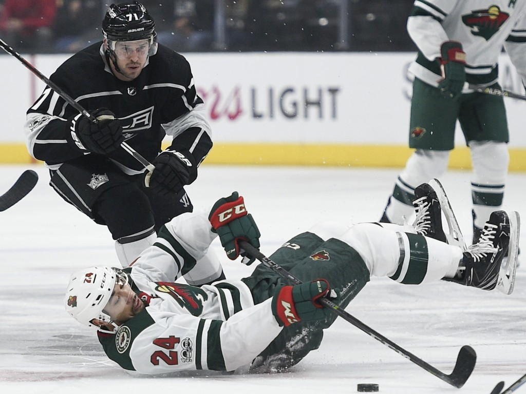 Minnesota Wild defenseman Matt Dumba falls to the ice in front of of Los Angeles Kings center Torrey Mitchell during the first period of an NHL hockey