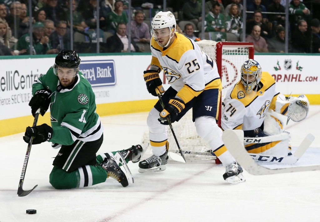 Dallas Stars left wing Curtis McKenzie (11) attempts to gain control of the puck as Nashville Predators' Alexei Emelin (25) and goalie Juuse Saros (74
