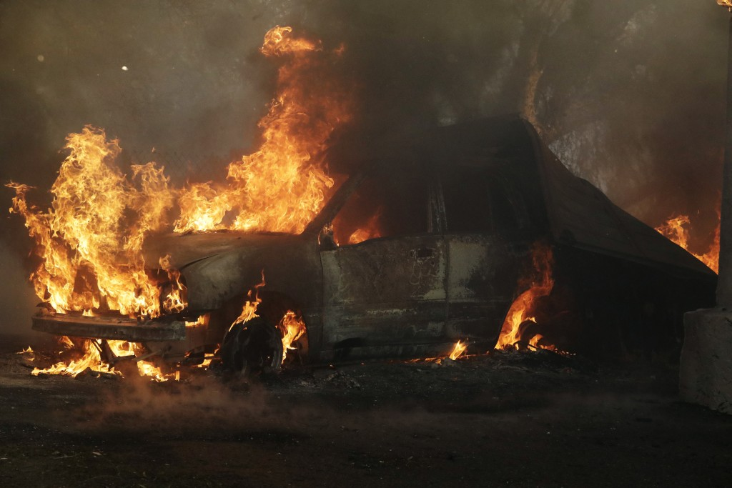 A car burns during a wildfire in the Lake View Terrace area of Los Angeles, Tuesday, Dec. 5, 2017. (AP Photo/Chris Carlson)