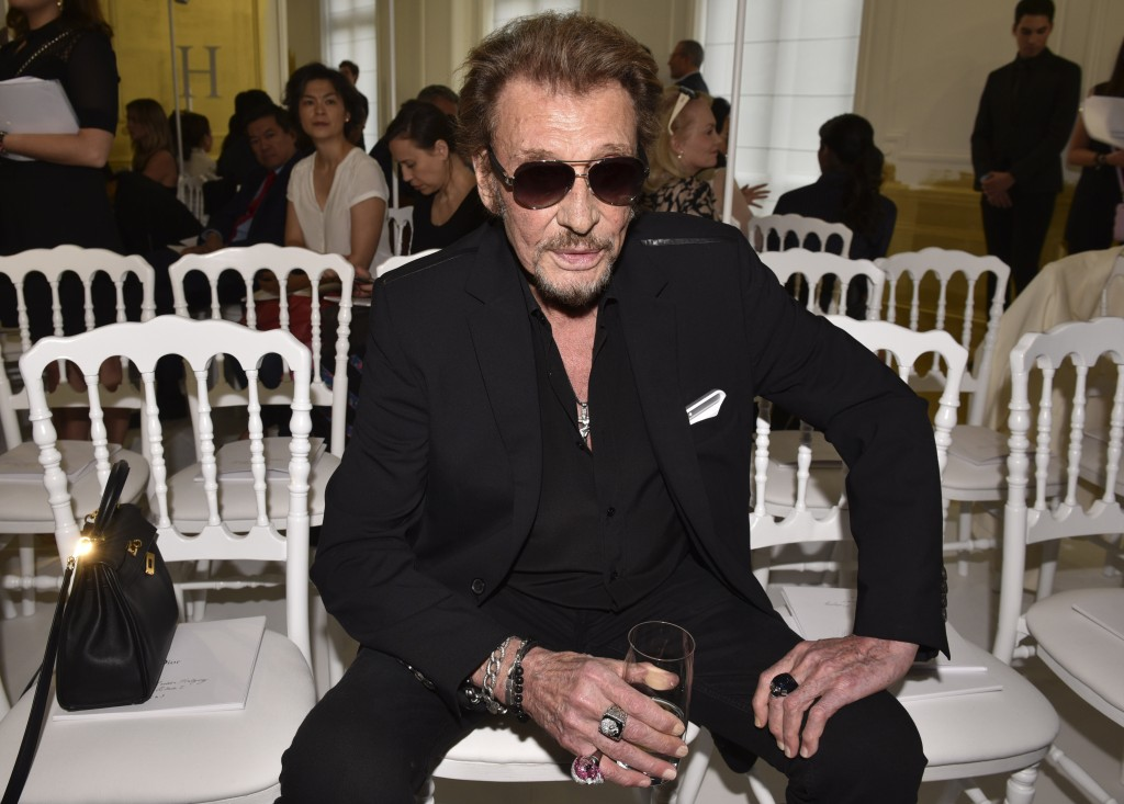 FILE - In this July 4, 2016 file picture, French rock singer Johnny Hallyday waits before Christian Dior's Haute Couture Fall-Winter 2016-2017 fashion