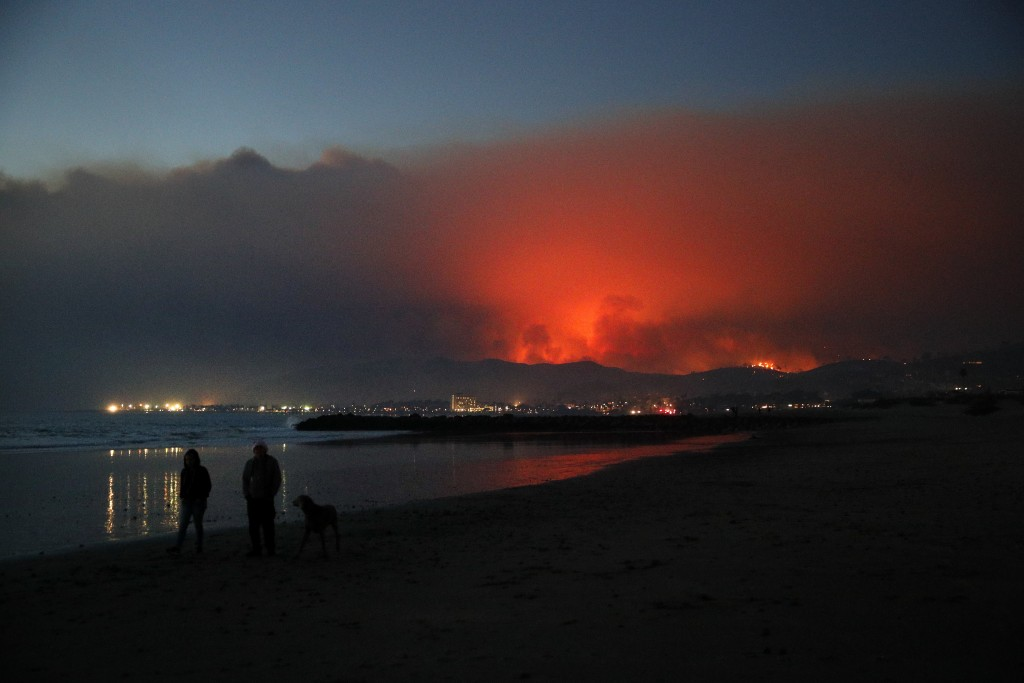 Two people walk along the beach with a dog as a wildfire burns in distance Tuesday, Dec. 5, 2017, in Ventura, Calif. Raked by ferocious Santa Ana wind