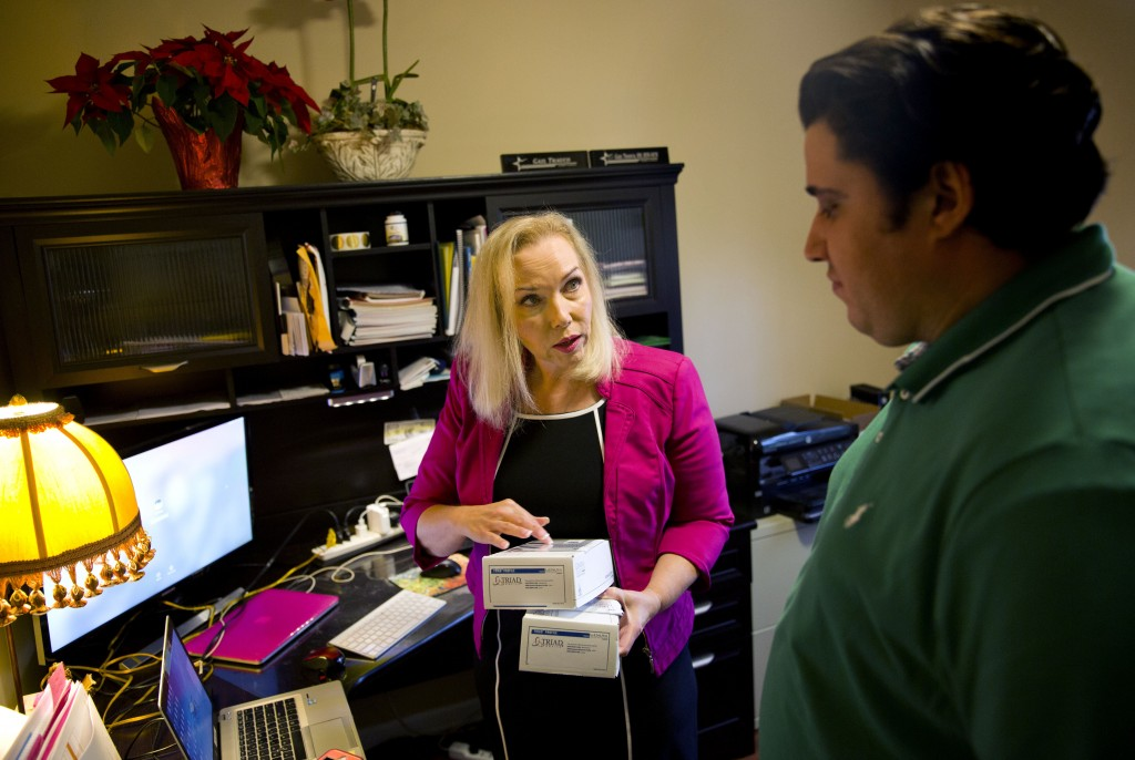 In this Monday, Dec. 4, 2017, photo, Gail Trauco, owner of The PharmaKon, left, talks with Jordan Rubio, her office manager and son, while working in