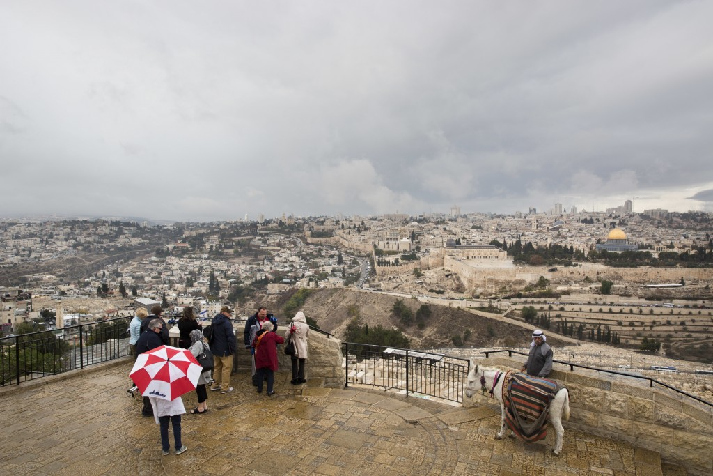 A group of tourists visit Mount of Olives overlooking the Old City in Jerusalem, Wednesday, Dec. 6, 2017. U.S. officials say President Donald Trump wi