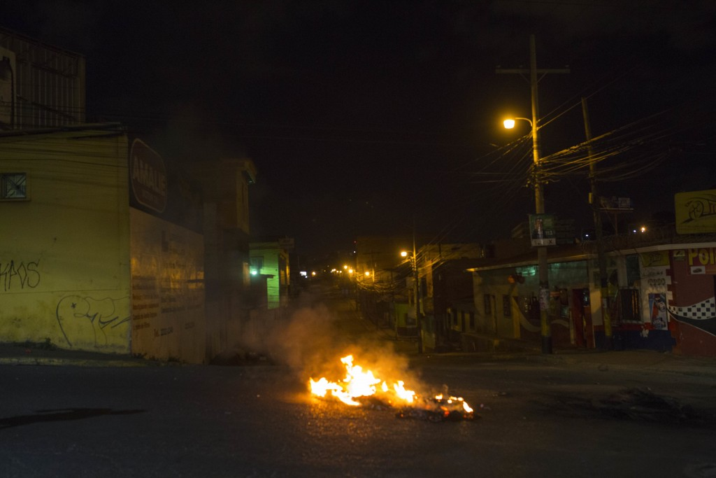 A barricade placed by anti-government demonstrators burns in protest during a government imposed dawn-to-dusk curfew in Tegucigalpa, Honduras, late Tu