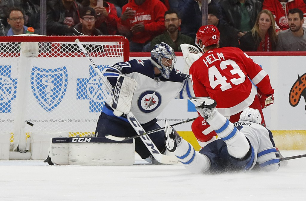 Detroit Red Wings left wing Darren Helm (43) scores on Winnipeg Jets goalie Connor Hellebuyck (37) in the third period of an NHL hockey game Tuesday,