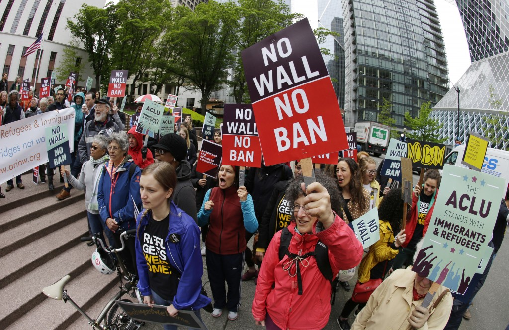 FILE - In this May 15, 2017, file photo, protesters wave signs and chant during a demonstration against President Donald Trump's revised travel ban ou