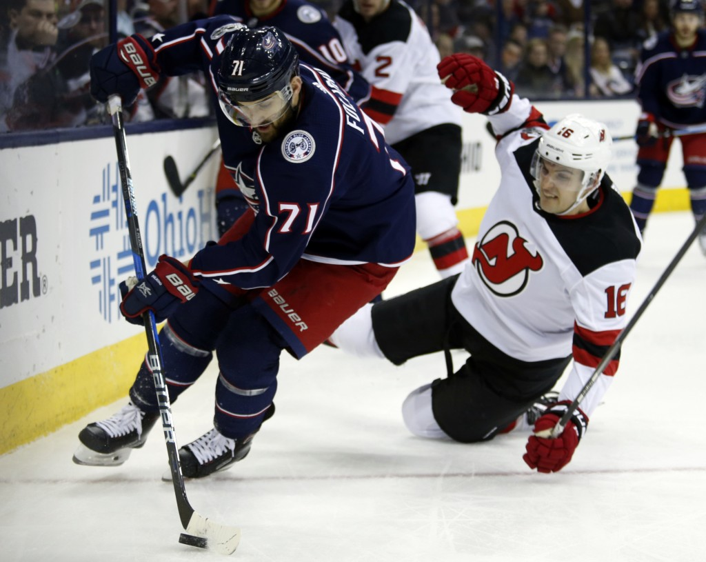 Columbus Blue Jackets forward Nick Foligno, left, controls the puck in front of New Jersey Devils defenseman Steven Santini during the second period o