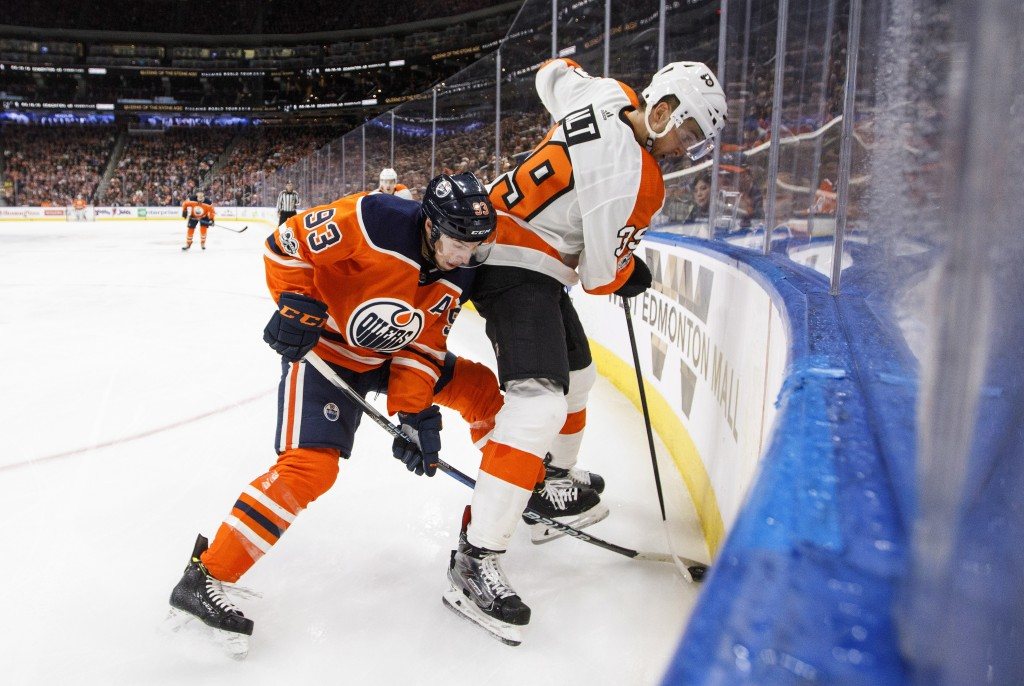 Philadelphia Flyers' Mark Alt (39) and Edmonton Oilers' Ryan Nugent-Hopkins (93) vie for the puck during the second period of an NHL hockey game Wedne
