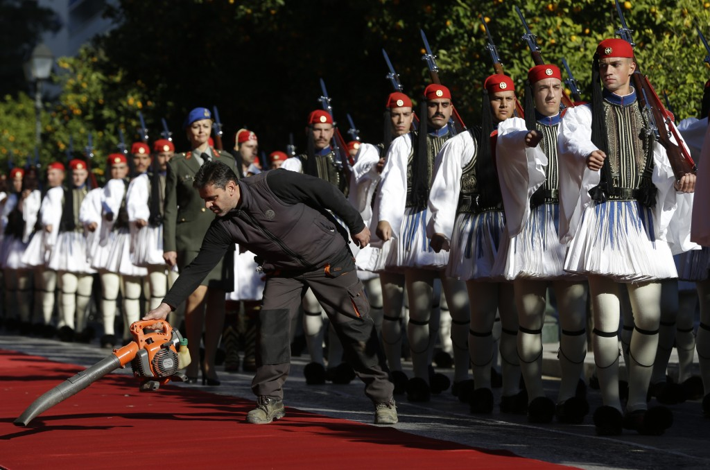 A worker cleans the red carpet as Greek Presidential Guards march to their positions for the official welcome ceremony for Turkey's President Recep Ta