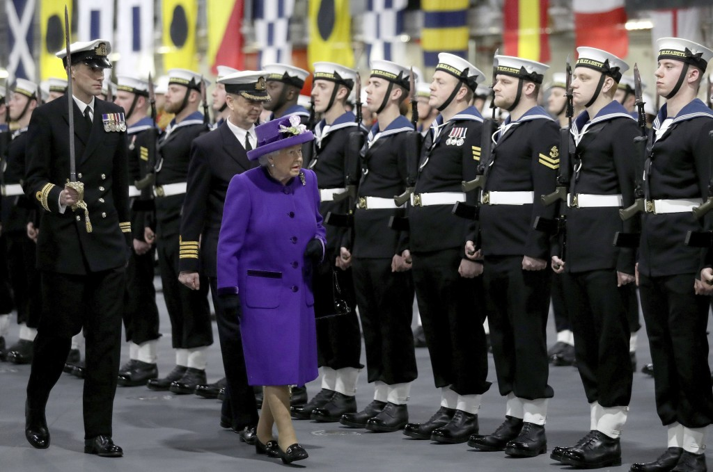 Britain's Queen Elizabeth II walks with the ship's commanding officer Captain Jerry Kyd, rear right,, as she arrives for the commissioning ceremony of