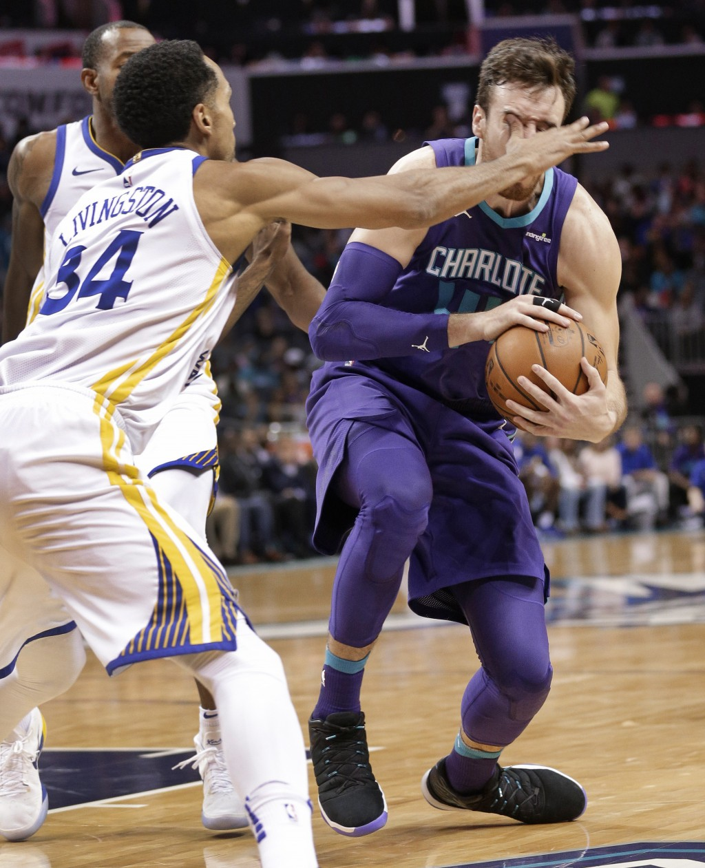 Charlotte Hornets' Frank Kaminsky, right, is poked in the eye by Golden State Warriors' Shaun Livingston (34) during the first half of an NBA basketba