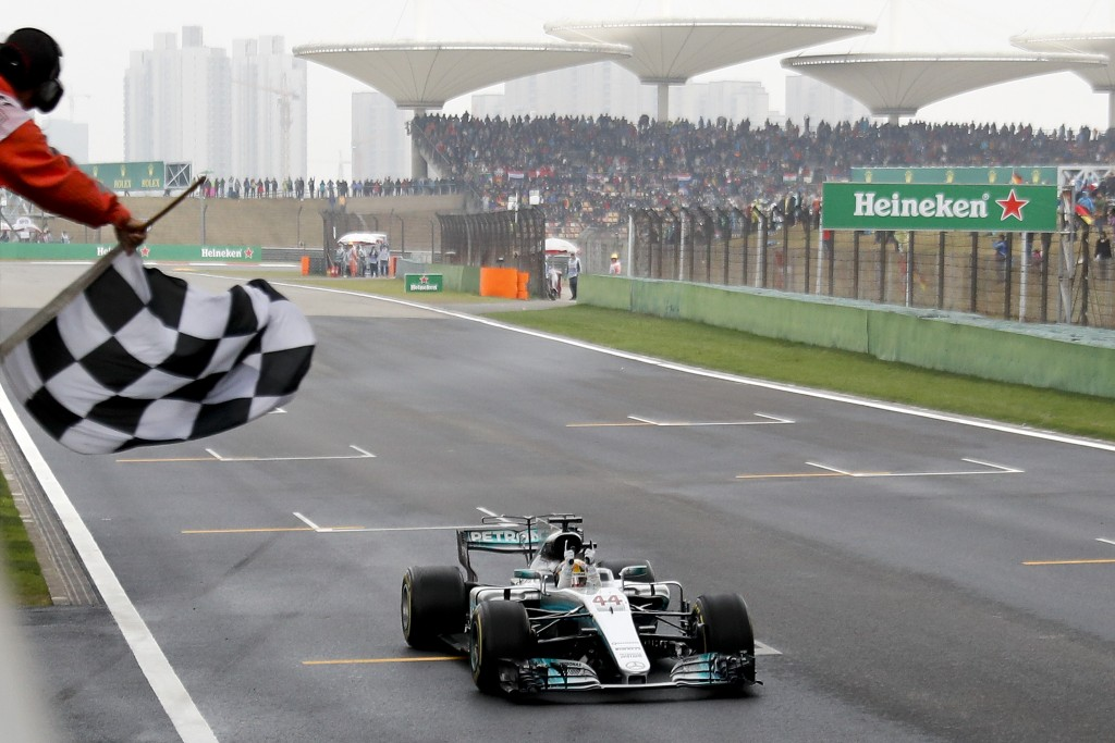 FILE - In this April 9, 2017, file photo, Mercedes driver Lewis Hamilton of Britain gets the checkered flag to win the Chinese Formula One Grand Prix
